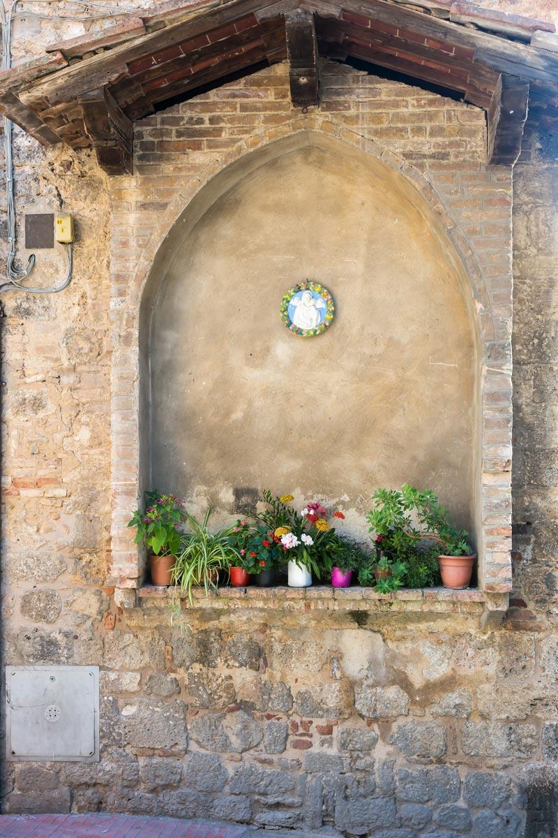 San Gimgnano - egy vakablak, egy szentkép és virágok