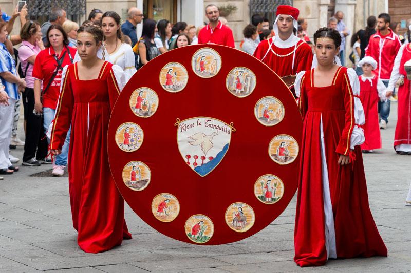Jelmezes, középkori felvonulás Aciano-ban. A képen az egyik kerület címere